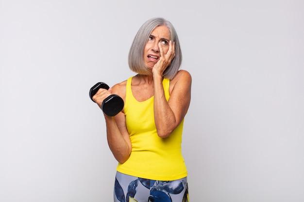 Женщина среднего возраста чувствует скуку, разочарование и сонливость после утомительной, скучной и утомительной работы, держась за лицо рукой. фитнес-концепция