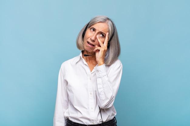中年の女性は、面倒で退屈で退屈な仕事をした後、退屈で欲求不満で眠くなり、顔を手で持っています。テレマーケティングの概念