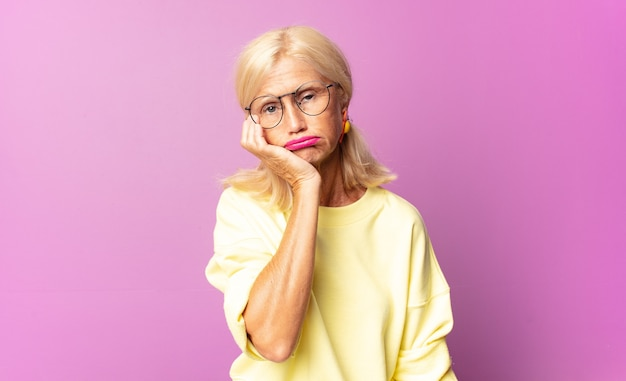 中年の女性は、手で顔を持って、退屈で、退屈で、退屈な仕事をした後、退屈、欲求不満、眠気を感じます