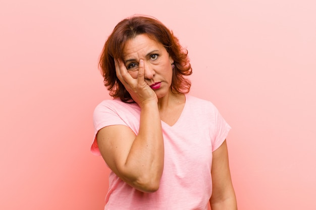 Middle age woman feeling bored, frustrated and sleepy after a tiresome, dull and tedious task, holding face with hand against pink wall