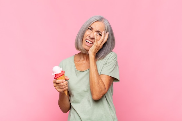 Middle age woman feeling bored, frustrated and sleepy after a tiresome, dull and tedious task, holding face with hand having an ice cream