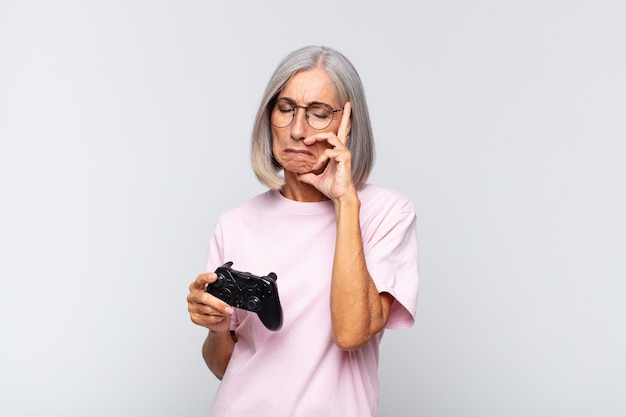 Middle age woman feeling bored, frustrated and sleepy after a tiresome, dull and tedious task, holding face with hand. playing console concept