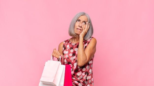 Middle age woman feeling bored, frustrated and sleepy after a tiresome, dull and tedious task, holding face with hand with shopping bags