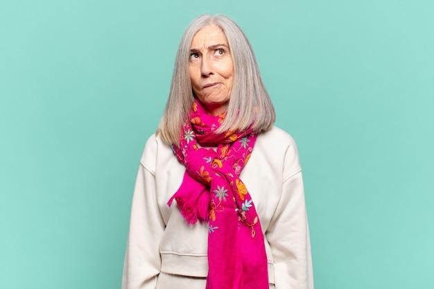 Женщина среднего возраста чувствует смущение и сомнение, задается вопросом или пытается выбрать или принять решение