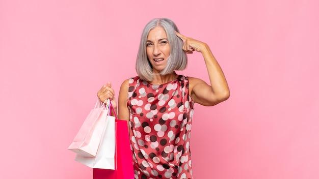 혼란스럽고 의아해하는 중년 여성, 쇼핑 가방으로 미쳤거나 미쳤거나 정신이 나간 것을 보여줍니다.