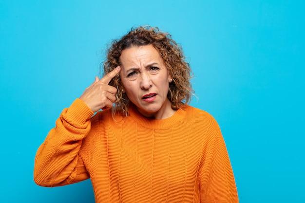 Женщина среднего возраста смущена и озадачена, показывая, что вы сошли с ума, сошли с ума или сошли с ума