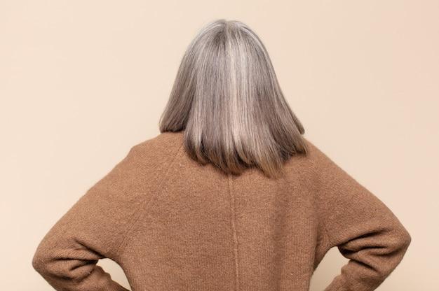 혼란 스럽거나 충만하거나 의심과 질문을 느끼는 중년 여성, 엉덩이에 손을 대고, 뒷모습