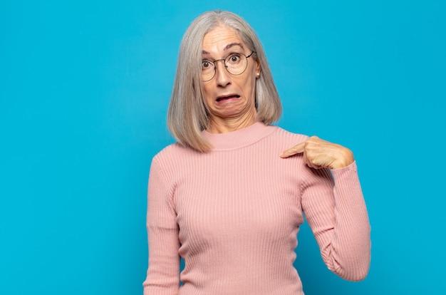 Женщина среднего возраста чувствует себя смущенной, озадаченной и неуверенной, указывая на себя, удивляясь и спрашивая, кто, я?