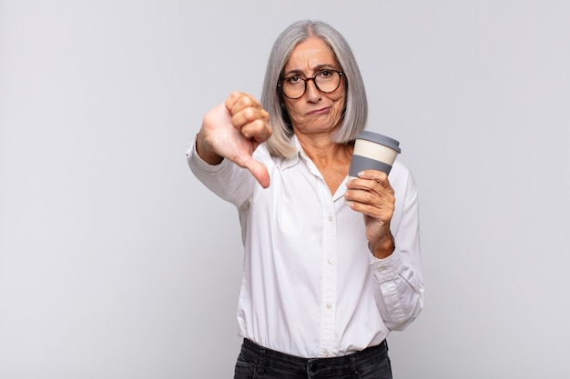 Middle age woman feeling cross, angry, annoyed, disappointed or displeased, showing thumbs down with a serious look coffee concept
