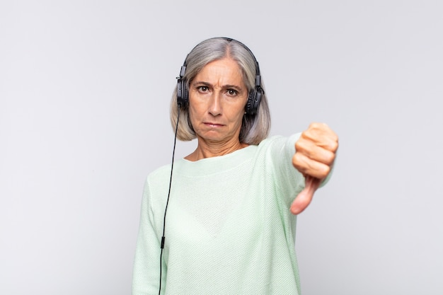 Middle age woman feeling cross, angry, annoyed, disappointed or displeased, showing thumbs down with a serious look