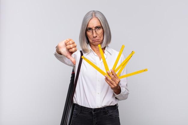 Женщина среднего возраста чувствует себя раздраженной, сердитой, раздраженной, разочарованной или недовольной изолированной