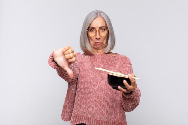 중간 나이 여자 느낌 십자가, 화가, 짜증, 실망 또는 불쾌, 심각한 표정으로 엄지 손가락을 보여주는 아시아 음식 개념