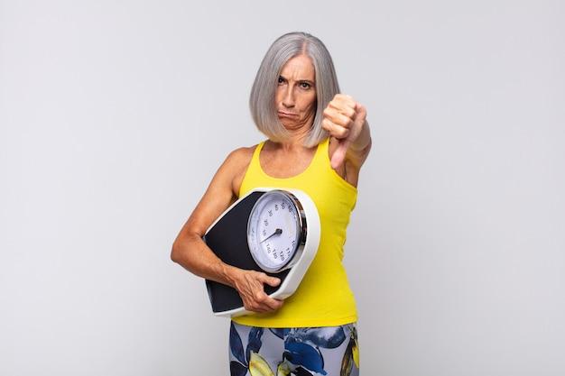 Женщина среднего возраста чувствует раздражение, злость, раздражение, разочарование или недовольство, показывая большой палец вниз серьезным взглядом. фитнес-концепция