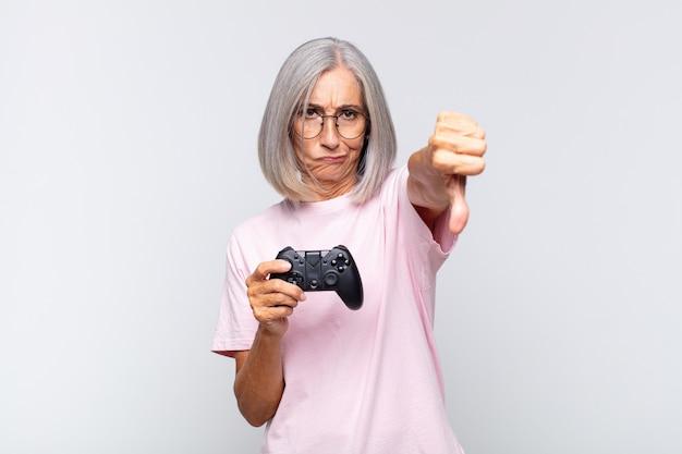 Женщина среднего возраста чувствует раздражение, злость, раздражение, разочарование или недовольство, показывая большой палец вниз с серьезным взглядом. концепция игровой консоли