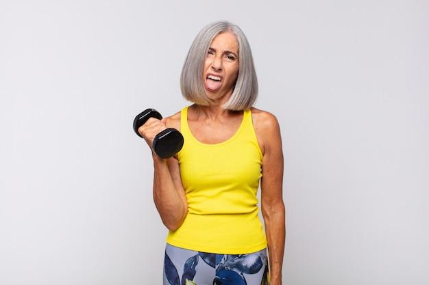 Женщина среднего возраста чувствует отвращение и раздражение, высовывает язык, не любит что-то противное и мерзкое. фитнес-концепция