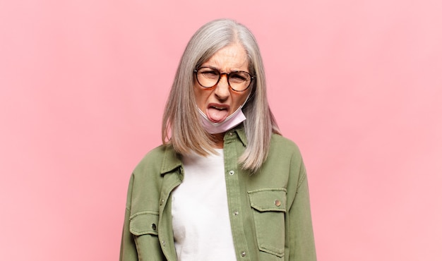 Женщина среднего возраста чувствует отвращение и раздражение, высовывает язык, не любит что-то противное и неприятное