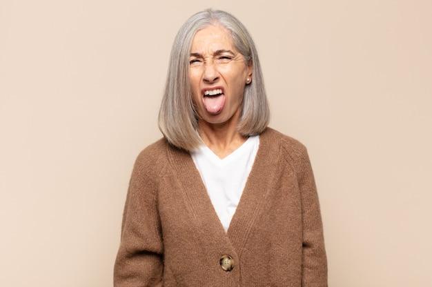 Женщина среднего возраста чувствует отвращение и раздражение, высовывает язык, не любит что-то противное и противное