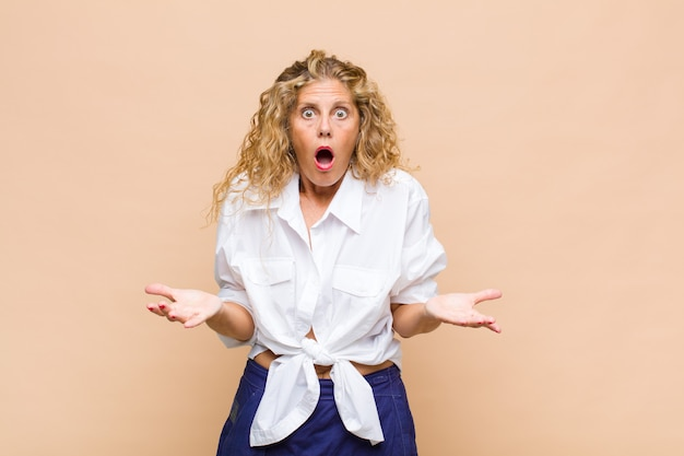 Женщина среднего возраста чувствует себя чрезвычайно шокированной и удивленной