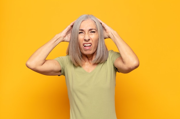 Middle age woman feeling frustrated and annoyed, sick and tired of failure, fed-up with dull, boring tasks