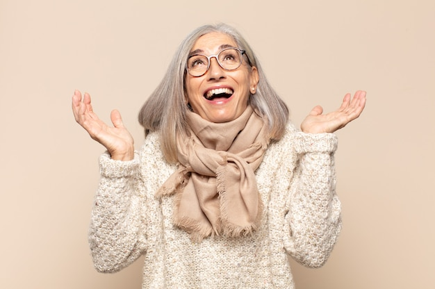 Женщина среднего возраста чувствует себя счастливой, пораженной, удачливой и удивленной, празднует победу с поднятыми вверх руками