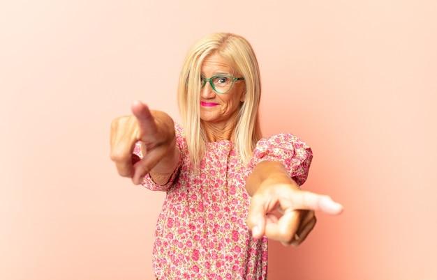 Женщина среднего возраста чувствует себя счастливой и уверенной, указывая на камеру обеими руками и смеясь, выбирая вас