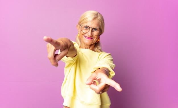 Женщина среднего возраста чувствует себя счастливой и уверенной, указывая обеими руками и смеясь, выбирая вас