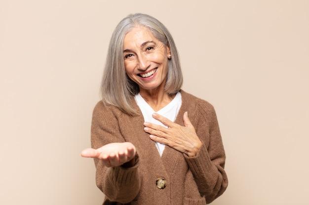 幸せと恋を感じ、片方の手で心の横に、もう片方の手で前に伸ばして笑っている中年女性