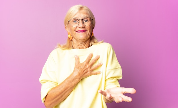 中年の女性は幸せと恋を感じ、片方の手で心の横に、もう片方の手で前に伸びて笑っている Premium写真