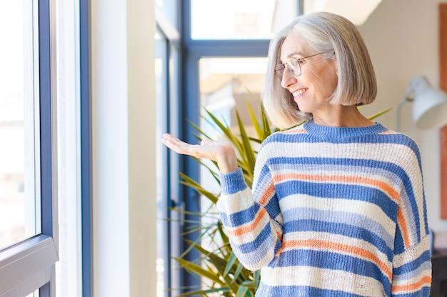 横に持っている物やコンセプトを見て、幸せでさりげなく笑顔を感じる中年女性