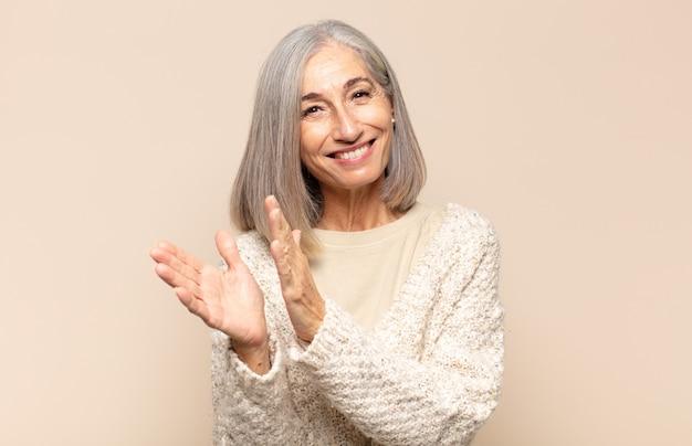 행복하고 성공한 중년 여성, 미소 짓고 손뼉을 치며 박수로 축하합니다