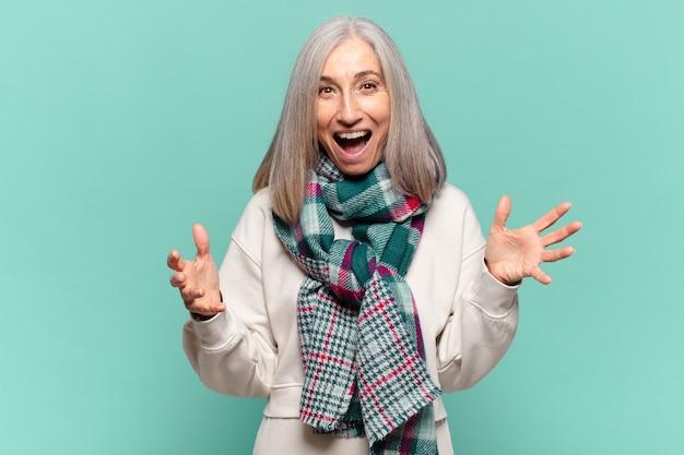 Женщина среднего возраста чувствует себя счастливой, удивленной, удачливой и удивленной, как будто серьезно говорит: «боже»? невероятный