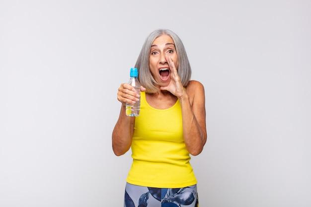 중년 여성이 행복하고 흥분되고 긍정적 인 느낌을 주며 입 옆에 손으로 큰 소리를 지르며 외칩니다. 피트니스 개념