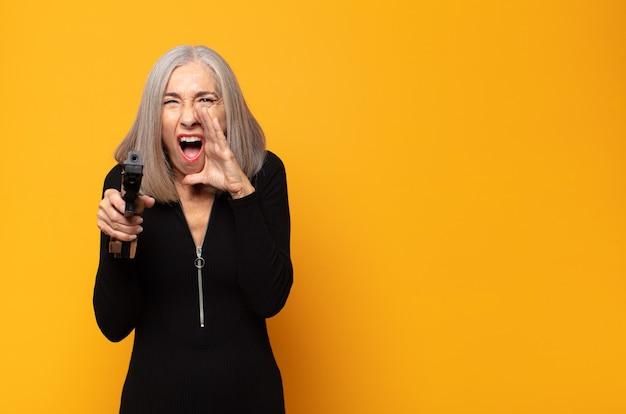 Женщина среднего возраста чувствует себя счастливой, взволнованной и позитивной, громко кричит, прижав руки ко рту, выкрикивая