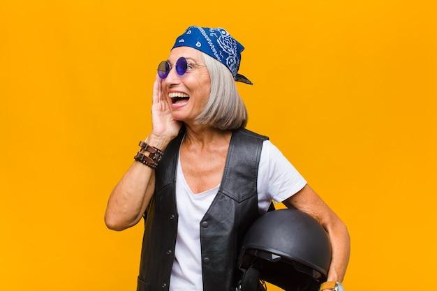 Женщина среднего возраста чувствует себя счастливой, взволнованной и удивленной, глядя в сторону обеими руками на лице