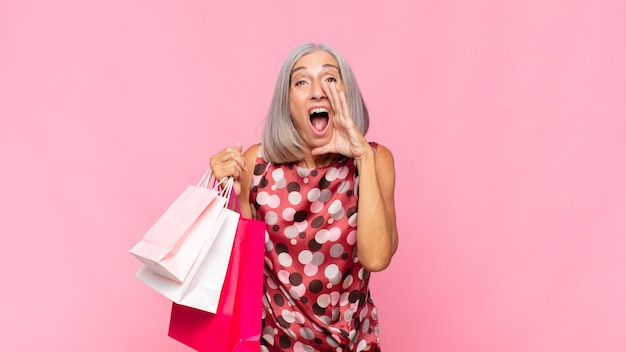 Middle age woman feeling happy, excited and positive, giving a big shout out with hands next to mouth, calling out with shopping bags