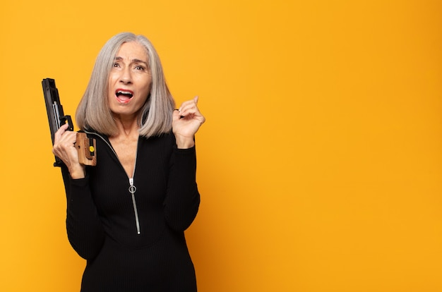 Middle age woman feeling happy, excited, surprised or shocked, smiling and astonished at something unbelievable