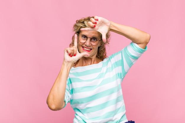 幸せで、友好的で、前向きで、笑顔で、手でポートレートやフォトフレームを作る中年の女性