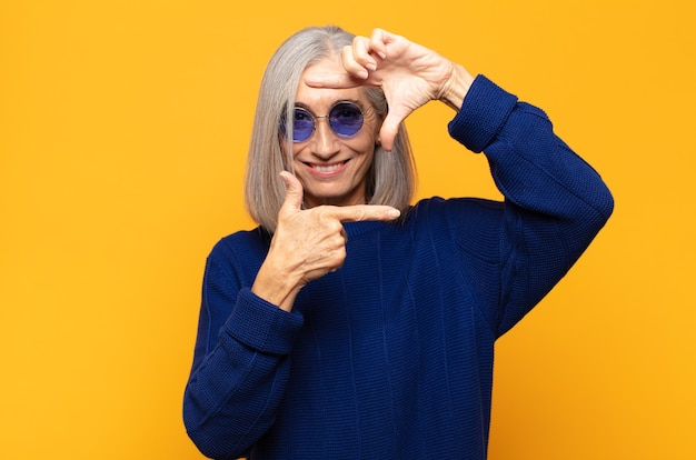 Женщина среднего возраста чувствует себя счастливой, дружелюбной и позитивной, улыбается и делает руками портрет или фоторамку