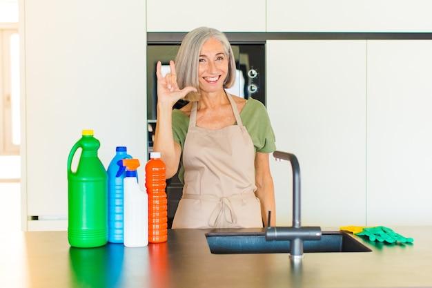 Женщина среднего возраста чувствует себя счастливой, веселой, уверенной, позитивной и мятежной, делает рукой знак рок или хэви-метал