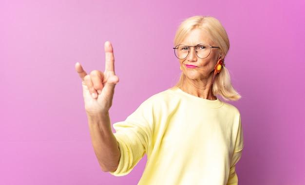 幸せ、楽しさ、自信、前向きで反抗的な感じ、手で岩や重金属の看板を作る中年の女性