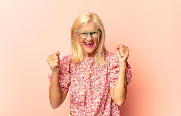 Женщина среднего возраста чувствует себя счастливой, позитивной и успешной, празднует победу изолированно