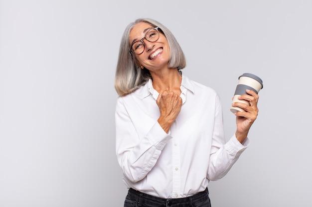 Женщина среднего возраста чувствует себя счастливой, позитивной и успешной, мотивированной, когда сталкивается с проблемой или празднует хорошие результаты.