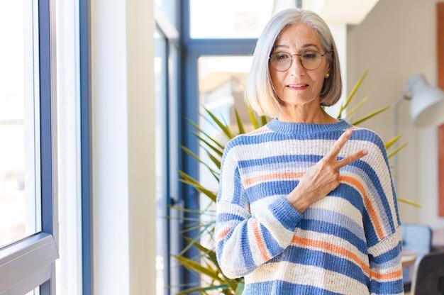 Женщина среднего возраста чувствует себя счастливой, позитивной и успешной, с рукой делает v-образную форму на груди, показывая победу или мир