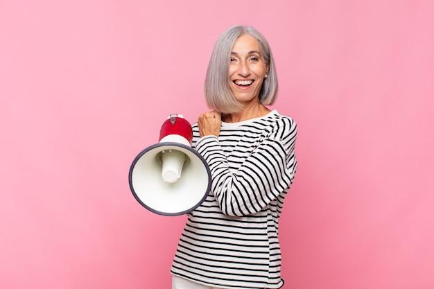 Женщина среднего возраста чувствует себя счастливой, позитивной и успешной