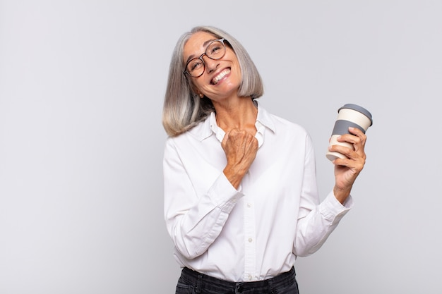 Middle age woman feeling happy, positive and successful, motivated when facing a challenge or celebrating good results coffee concept