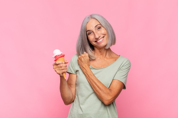 Middle age woman feeling happy, positive and successful, motivated when facing a challenge or celebrating good results having an ice cream