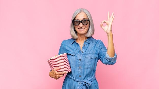 중년 여성이 행복하고 편안하고 만족감을 느끼고 괜찮은 제스처로 승인을 보여주고 영화 개념을 웃고 있습니다.