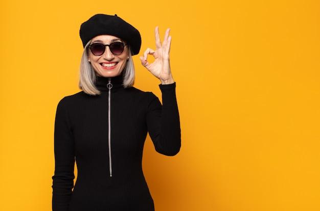 중년 여성이 행복하고 편안하고 만족스럽고 괜찮은 제스처로 승인을 보여주는 미소