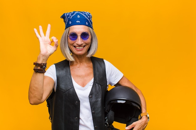 Middle age woman feeling happy, relaxed and satisfied, showing approval with okay gesture, smiling