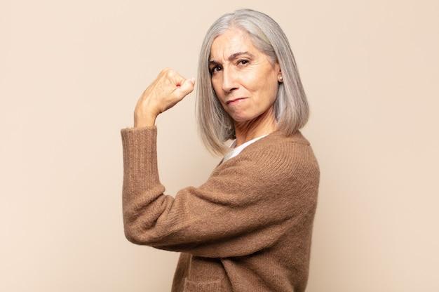 幸せ、満足、パワフル、屈曲フィット、筋肉の上腕二頭筋を感じ、ジムの後に強く見える中年女性